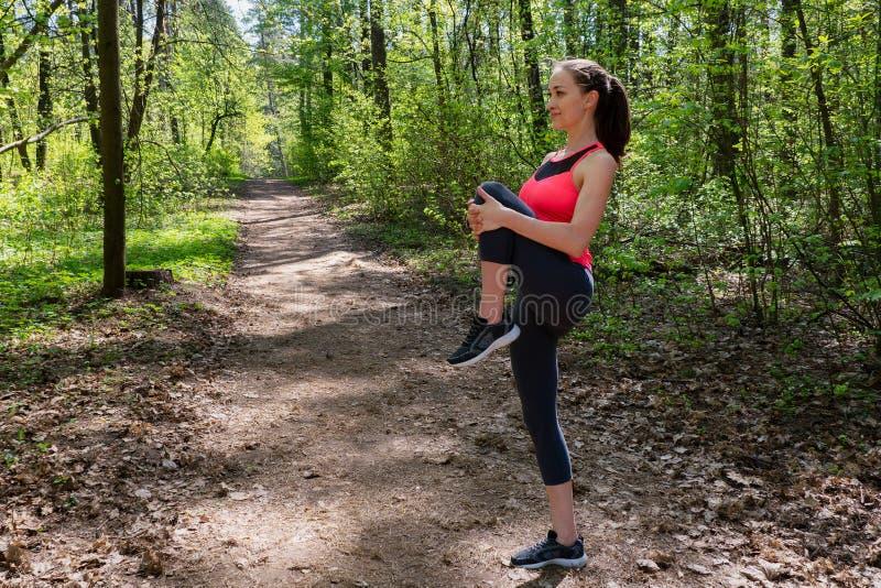 Corridore della donna che fa esercizio di riscaldamento prima del pareggiare nella foresta immagini stock
