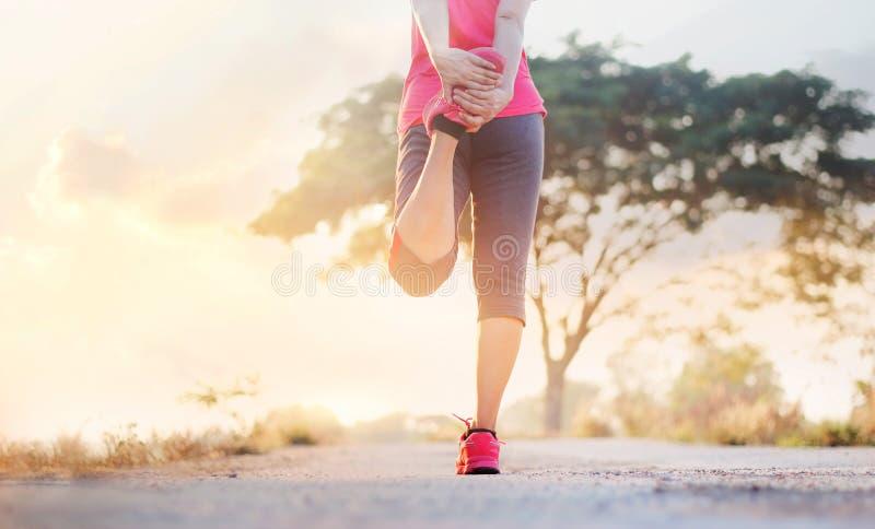 Corridore della giovane donna che allunga le gambe prima dell'correre nel tramonto rurale immagine stock libera da diritti