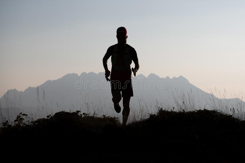 Corridore della montagna in siluetta in un paesaggio indicativo fotografie stock