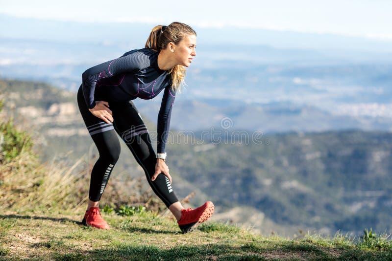 Corridore della traccia che allunga mentre guardando paesaggio dal picco di montagna immagini stock libere da diritti