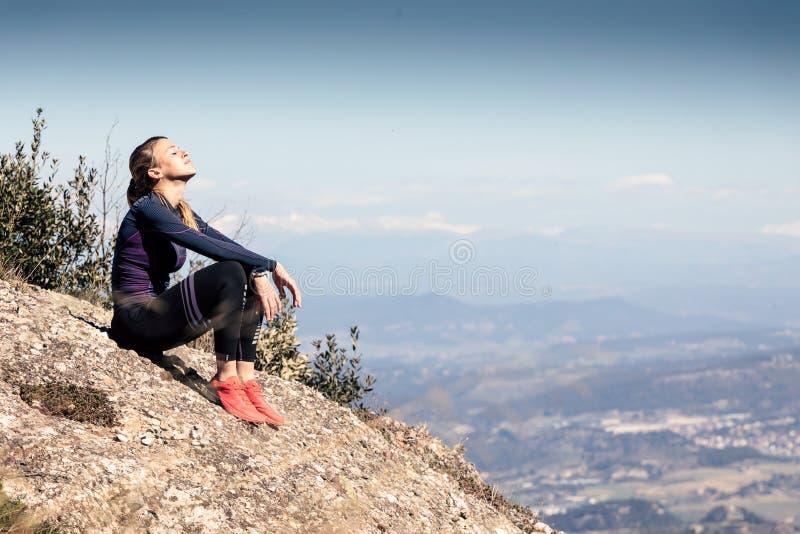 Corridore della traccia che si siede e che prende una rottura mentre guardando paesaggio dal picco di montagna immagine stock libera da diritti