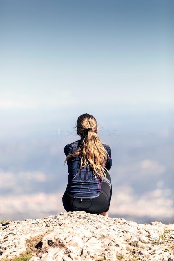 Corridore della traccia che si siede e che prende una rottura mentre guardando paesaggio dal picco di montagna fotografia stock