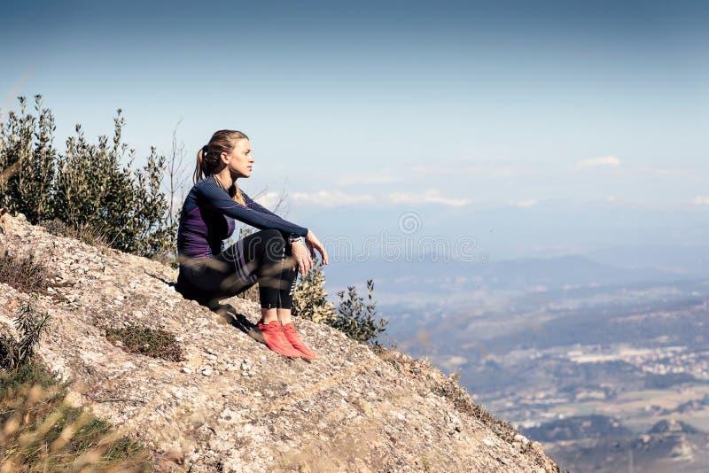 Corridore della traccia che si siede e che prende una rottura mentre guardando paesaggio dal picco di montagna immagini stock