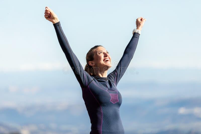 Corridore della traccia con a braccia aperte alzato mentre godendo della natura sul picco di montagna fotografia stock libera da diritti
