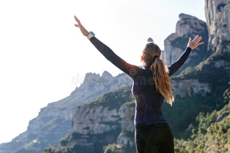 Corridore della traccia con a braccia aperte alzato mentre godendo della natura sul picco di montagna immagine stock libera da diritti