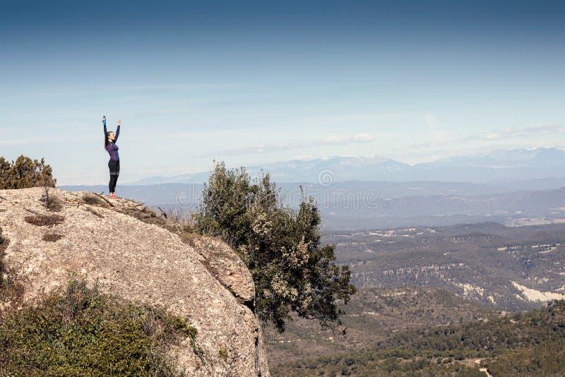 Corridore della traccia con a braccia aperte alzato mentre godendo della natura sul picco di montagna fotografia stock