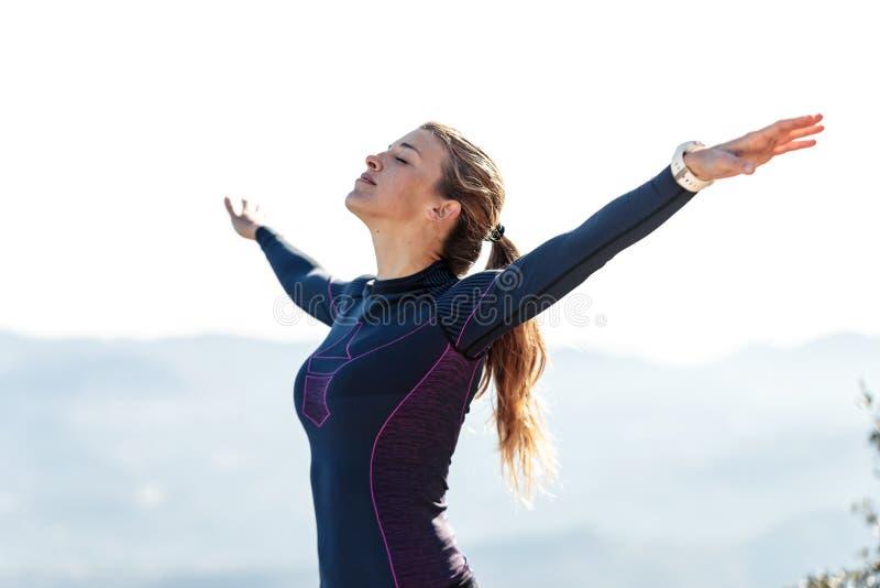 Corridore della traccia con a braccia aperte alzato mentre godendo della natura sul picco di montagna immagine stock