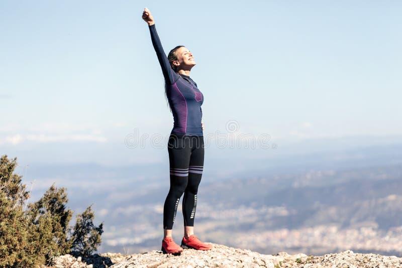 Corridore della traccia con a braccia aperte alzato mentre godendo della natura sul picco di montagna immagini stock