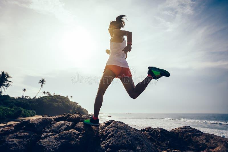 Corridore della traccia della donna che corre alla cima della montagna rocciosa fotografia stock libera da diritti