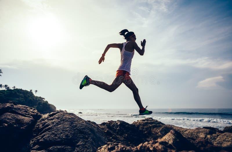 Corridore della traccia della donna che corre alla cima della montagna rocciosa fotografia stock