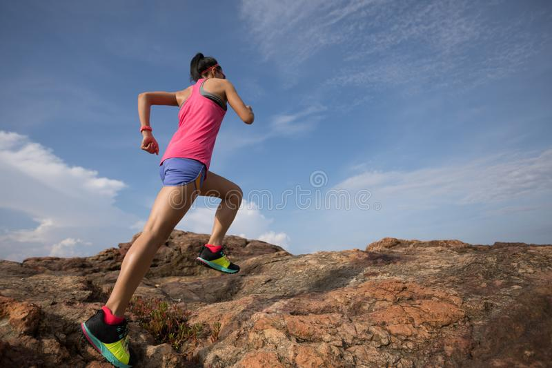 Corridore della traccia della donna che corre alla cima della montagna rocciosa sulla spiaggia fotografie stock libere da diritti