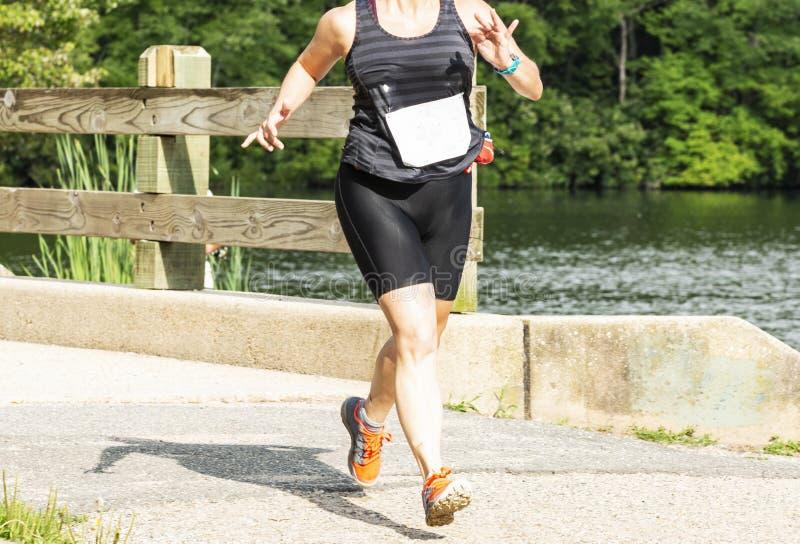Corridore delle donne che corre un 10K sopra un ponte intorno ad un lago fotografie stock