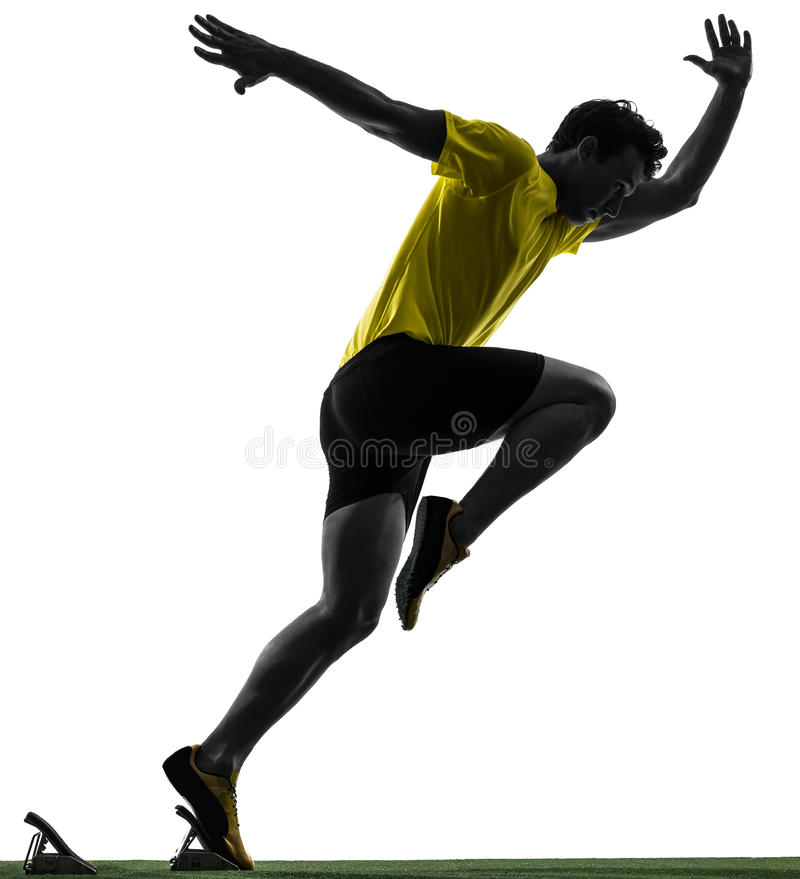 Corridore dello sprinter del giovane nella siluetta dei blocchetti iniziare fotografia stock