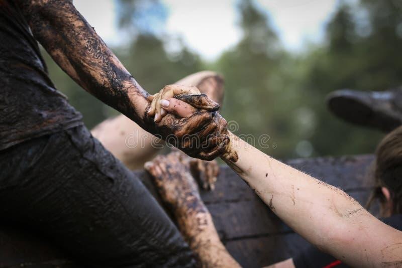 Corridore di corsa fangoso di ostacolo nell'azione Funzionamento del fango immagini stock libere da diritti