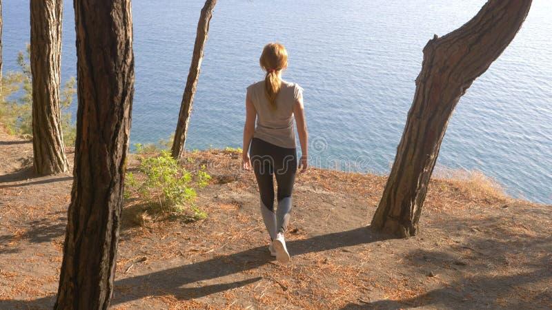 Corridore di forma fisica della donna su successo felice e di celebrazione superiore la donna gode della vista del mare dalla mon fotografie stock
