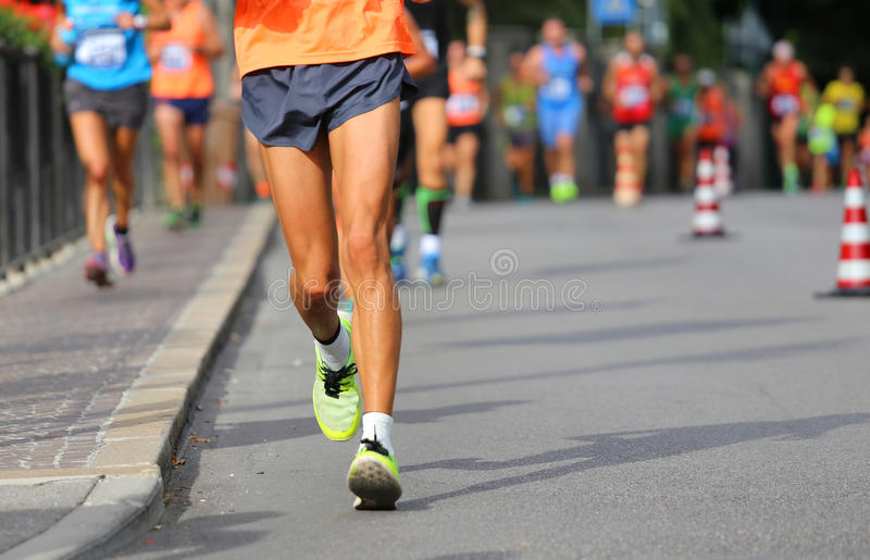 Corridore durante la camminata di corsa nella città con molti atleti immagini stock