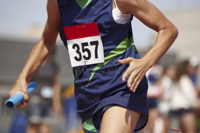 Corridore femminile che finisce una corsa di relè in una pista corrente fotografia stock