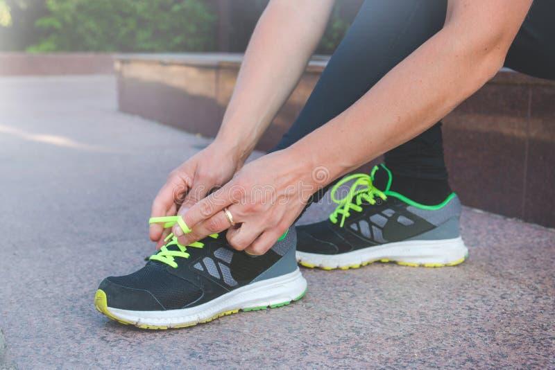 Corridore femminile che lega le sue scarpe che preparano per un funzionamento un trotto fuori fotografia stock