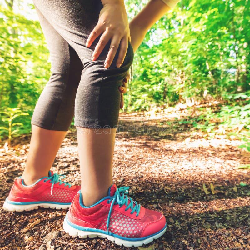 Corridore femminile con la ferita al ginocchio fotografie stock