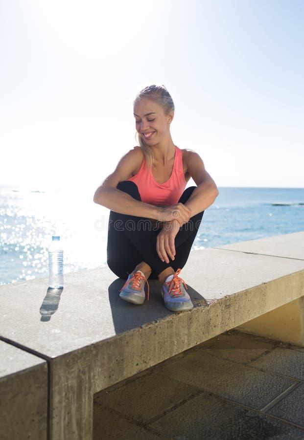 Corridore femminile felice che si rilassa dopo l'addestramento di forma fisica nell'aria fresca nel giorno soleggiato fotografie stock
