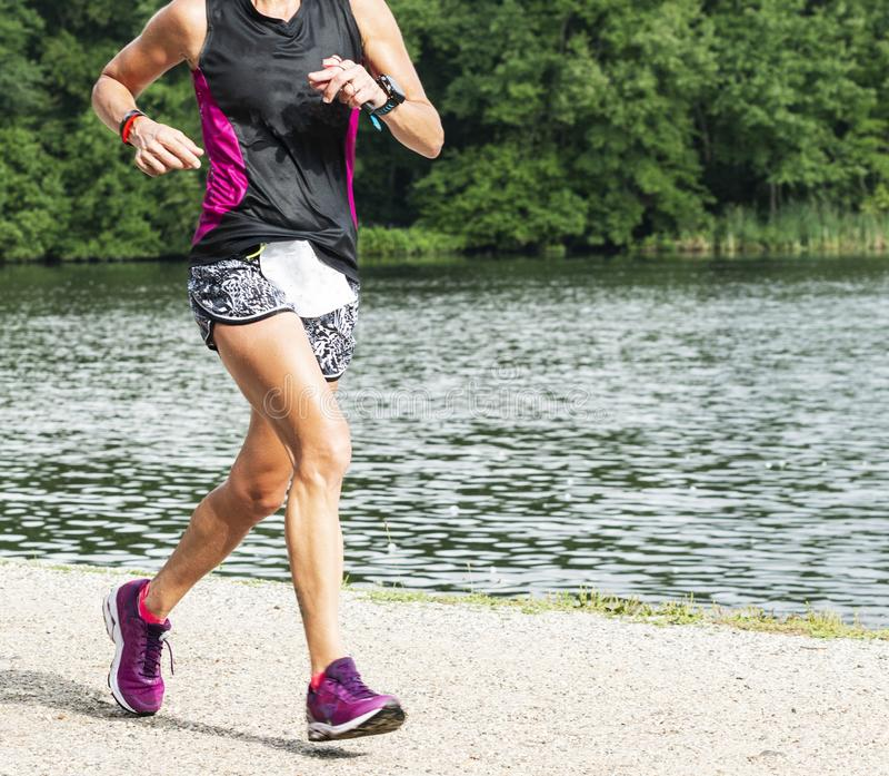 Corridore femminile 10K di corsa su una traccia intorno ad un lago immagine stock