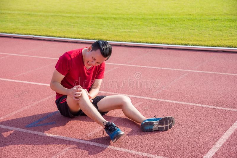 Corridore giovane che ha dolore al ginocchio fra funzionamento fotografie stock