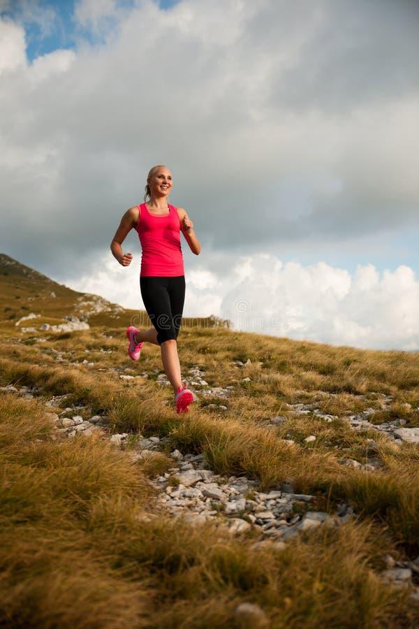 Corridore - la donna governa il paese delle Ass.Comm. su un percorso in autunno in anticipo immagini stock