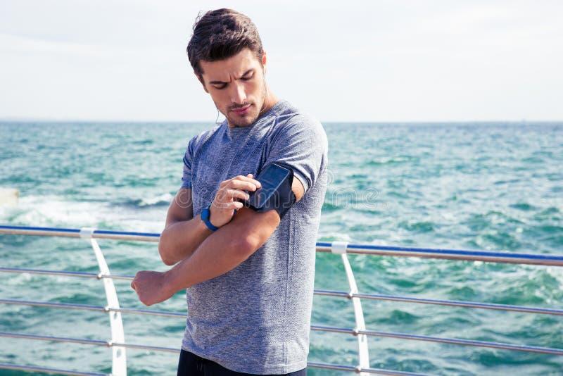 Corridore maschio che ascolta la musica che registra le regolazioni sul bracciale per ottenere lo smartphone immagini stock libere da diritti