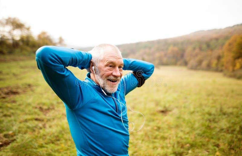 Corridore senior con il bracciale che fa allungamento Natura di autunno fotografie stock libere da diritti
