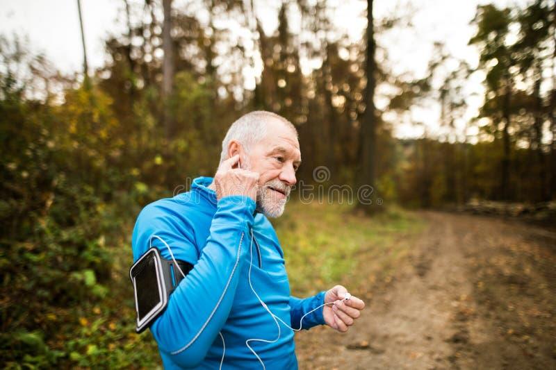 Corridore senior in natura con lo Smart Phone e le cuffie fotografie stock
