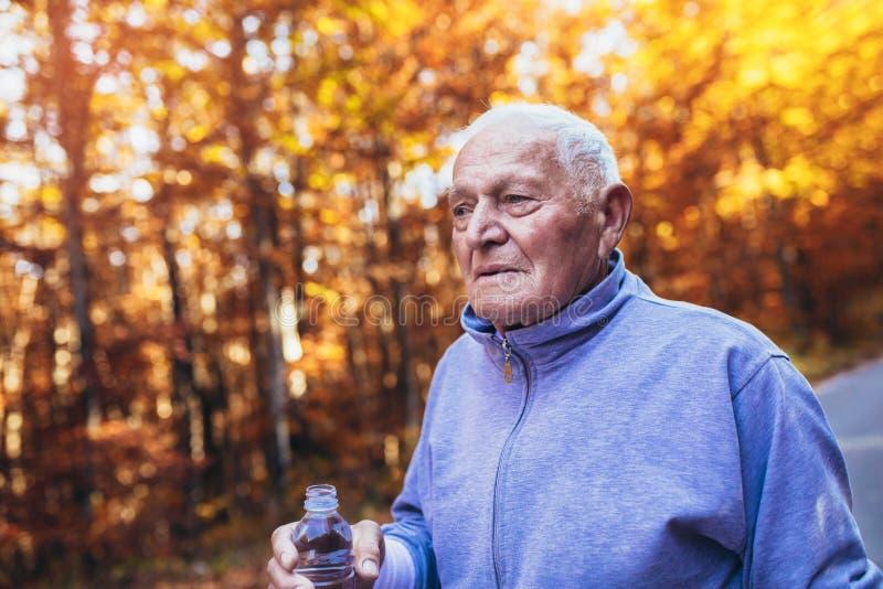 Corridore senior in natura Uomo sportivo anziano che corre nella foresta durante l'allenamento di mattina immagine stock
