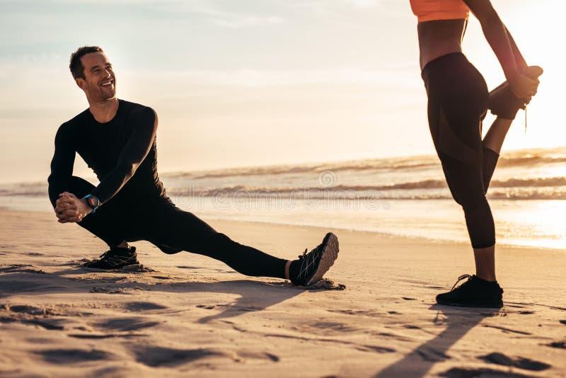 Corridori che fanno riscaldamento prima dell'correre alla spiaggia fotografia stock libera da diritti