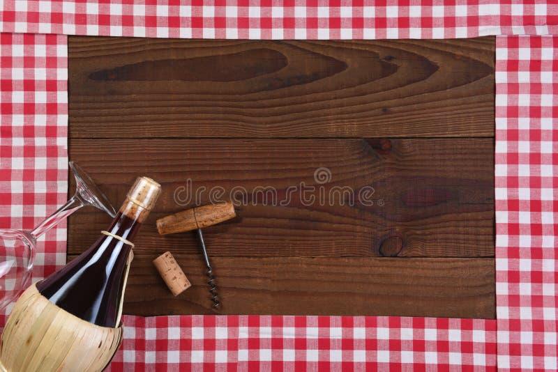 Corridori controllati rossi e bianchi della tavola che formano una struttura con una bottiglia del canestro del vino di Chianti immagine stock libera da diritti