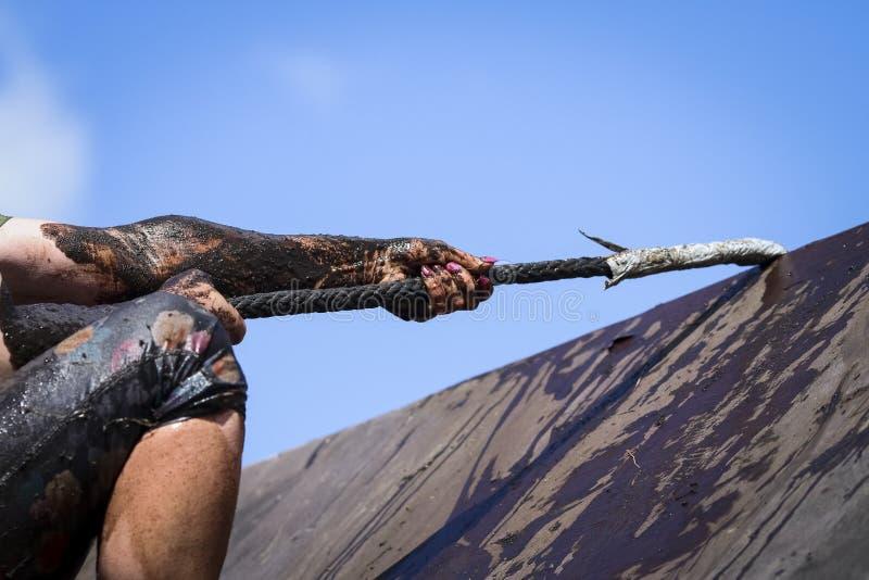 Corridori di corsa del fango, sconfiggenti gli ostacoli usando corda immagine stock libera da diritti