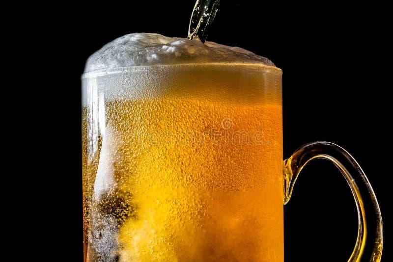 Corriente de la cerveza que vierte en un vidrio con la cerveza y la espuma aislada en el fondo negro, textura del primer imagenes de archivo