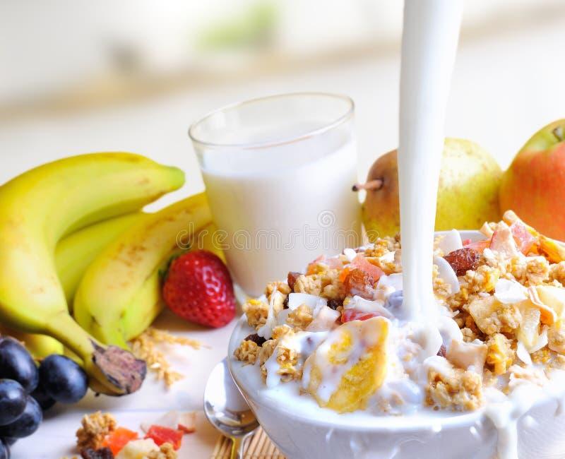 Corriente de la leche que cae en un cuenco de cereal y de frutas fotografía de archivo libre de regalías