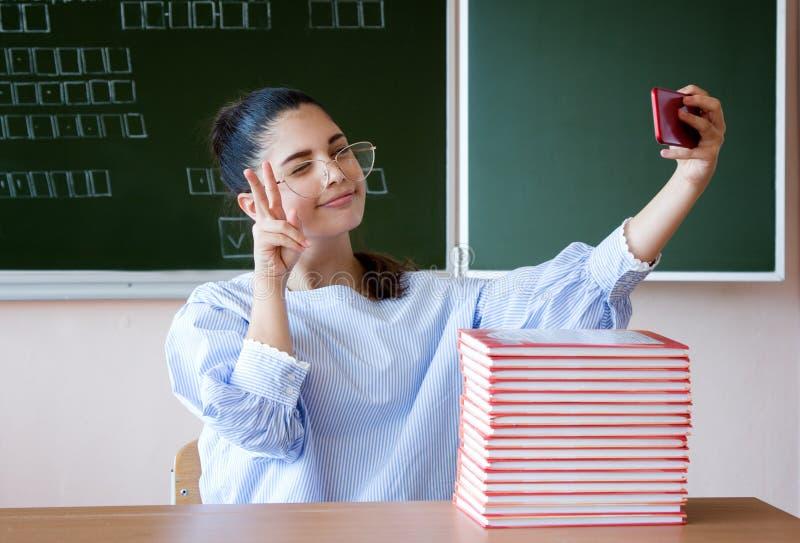 Corriente de Vlogger en línea Localización del estudiante contra la pizarra en sala de clase y hacer la muestra de la victoria imágenes de archivo libres de regalías