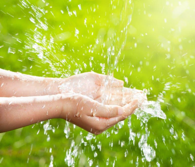 Corriente del agua potable que vierte en los niños las manos imagen de archivo