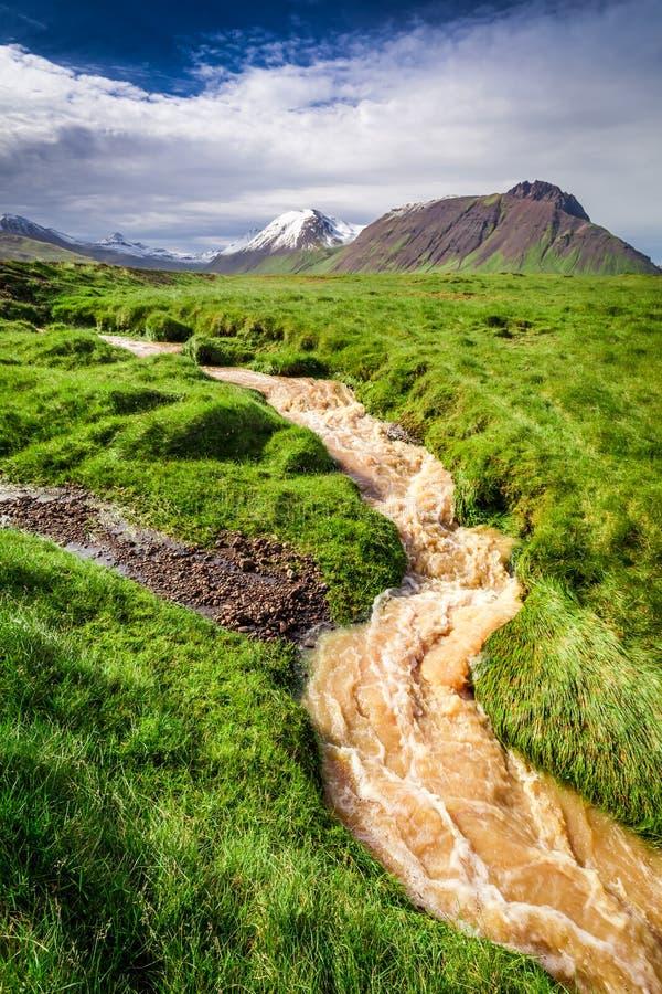 Corriente del agua que fluye de las montañas después de la lluvia, Islandia imagenes de archivo