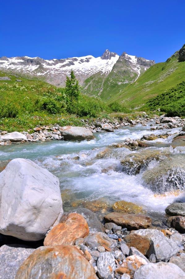 Corriente en valle alpino debajo del cielo azul fotografía de archivo libre de regalías