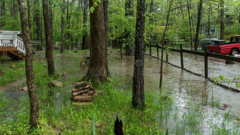 Corriente que desborda y que inunda la yarda despu?s de un temporal de lluvia imagenes de archivo