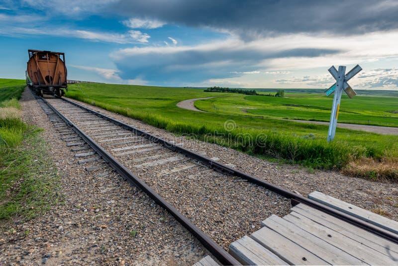 Corriente rápida, SK/Canada- 1 de julio de 2019: Extremo de la línea de coches de tren en el cruce ferroviario en Saskatchewan, C foto de archivo libre de regalías