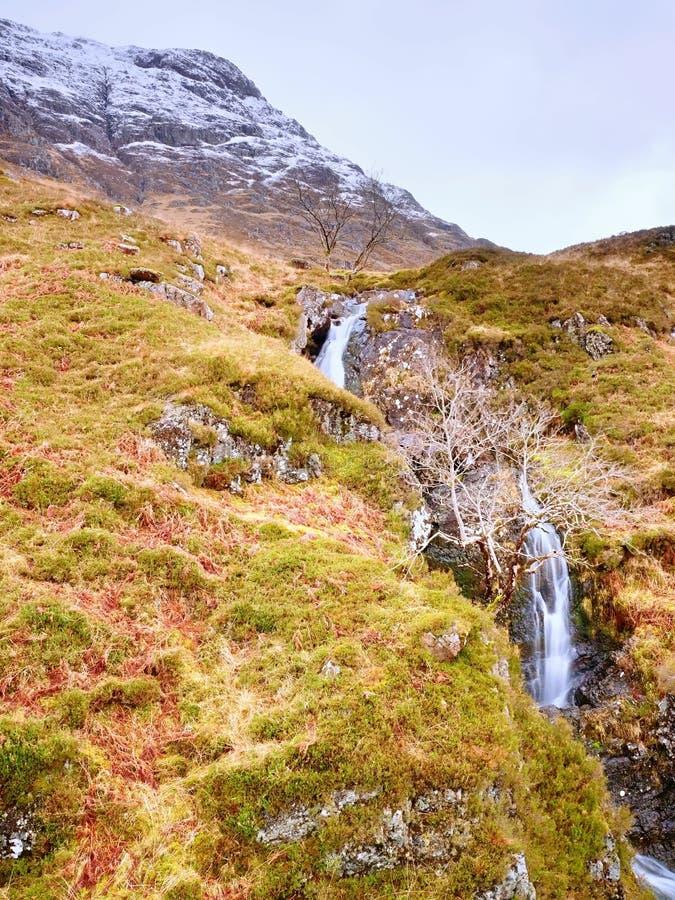 Corriente salvaje del paisaje de las montañas en frente Picos de montaña nevosos blancos y nubes grises fotografía de archivo