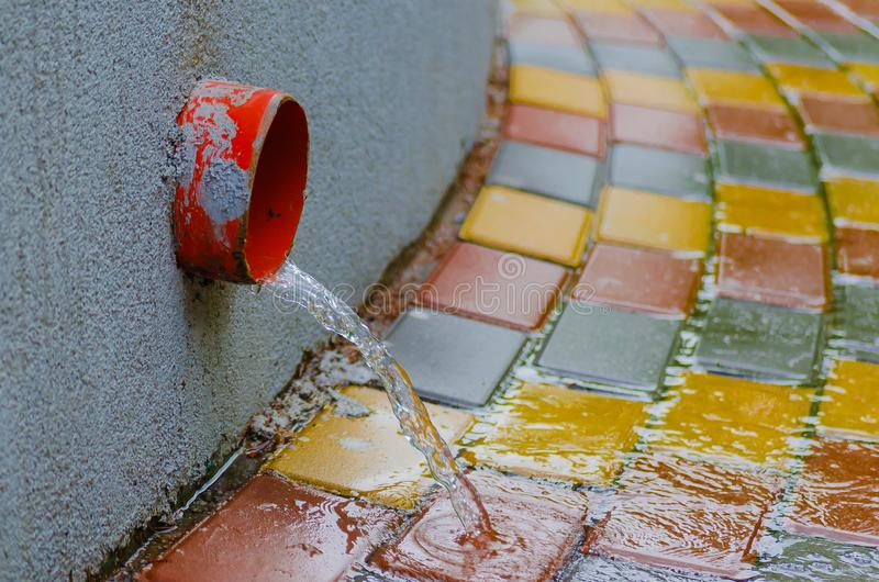 Corrientes abajo de la acera a lo largo de un tubo de drenaje durante la lluvia de primavera fotos de archivo libres de regalías