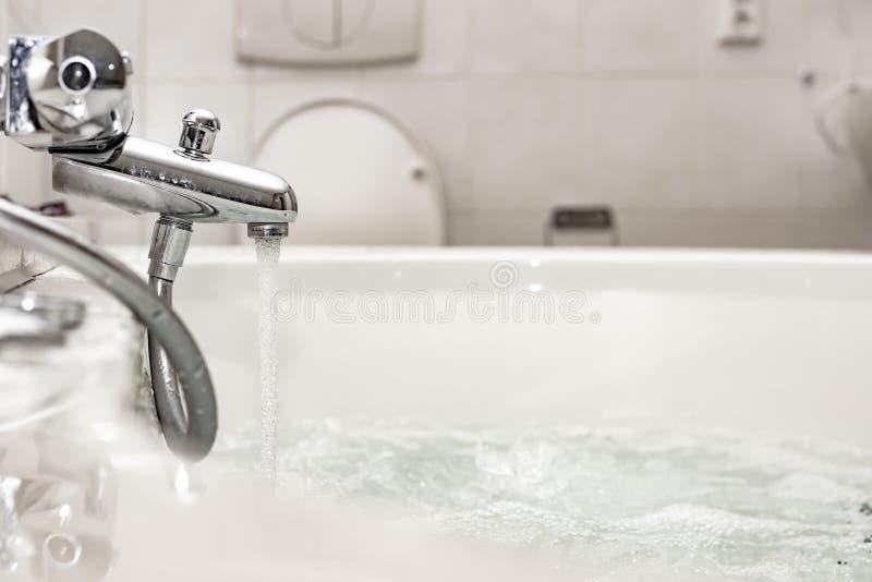 Corrientes de un mezclador del cromo a un baño o a un torbellino lujoso del balneario, con las burbujas de aire a relajarse Cuart fotos de archivo libres de regalías