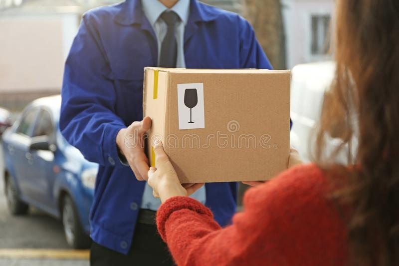 Corriere che dà pacchetto al cliente, fotografie stock