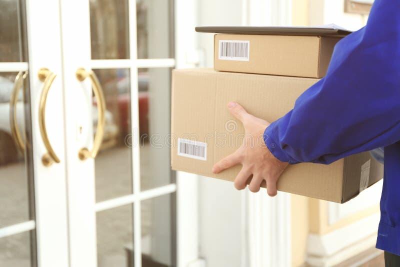 Corriere con i pacchetti sul gradino della porta, fotografie stock