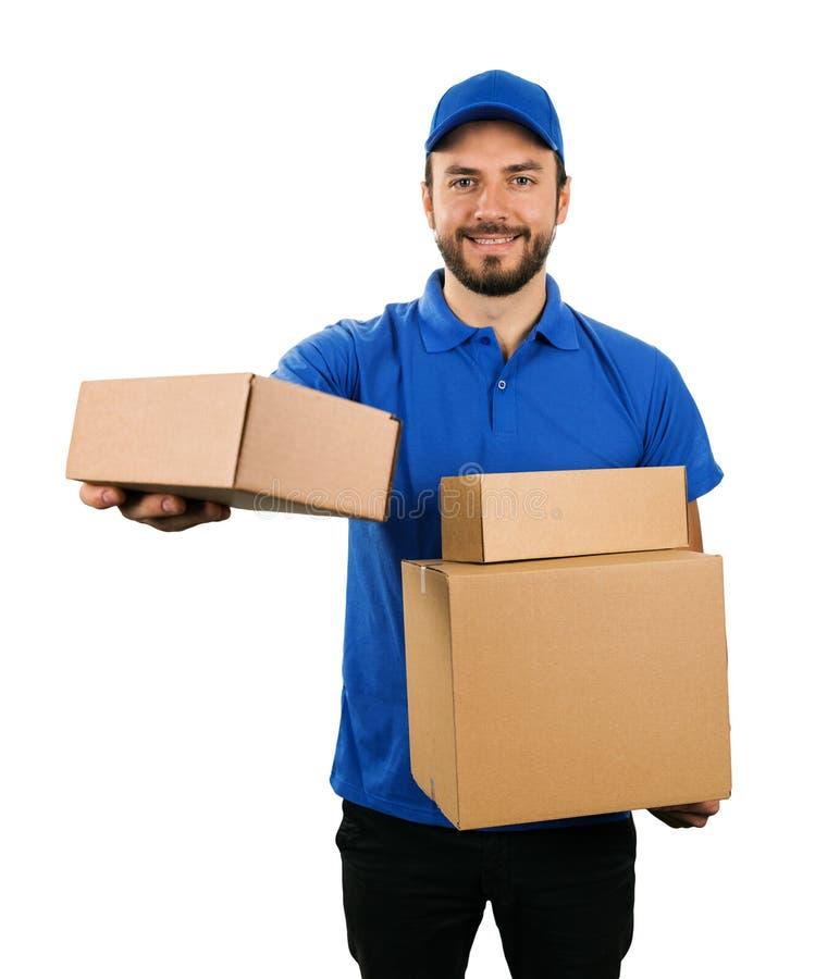 Corriere di consegna che dà la scatola di spedizione del cartone su fondo bianco immagini stock