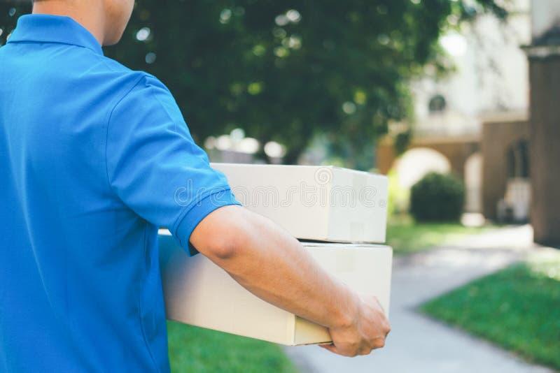 Corriere di servizio di distribuzione che sta davanti alla casa con la scatola fotografie stock libere da diritti