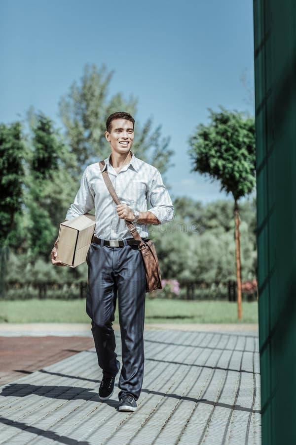 Corriere maschio allegro che esegue consegna al gradino della porta fotografie stock